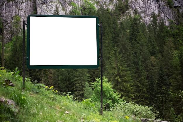 Рекламный щит с пустым белым макетом в зеленом лесу гор.