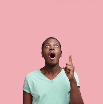 광고 개념. 캐주얼 의류에 놀란 잘 생긴 젊은 흑인 남성, 복사 공간이있는 빈 벽에 손가락을 가리 킵니다.