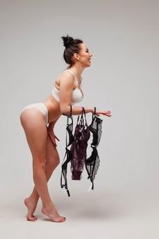 Рекламная концепция женского нижнего белья, выбор размера и модели бюстгальтера. молодая сексуальная брюнетка держит в руке бюстгальтеры повседневного использования. пустое пространство для текста на светло-сером фоне. копировать пространство