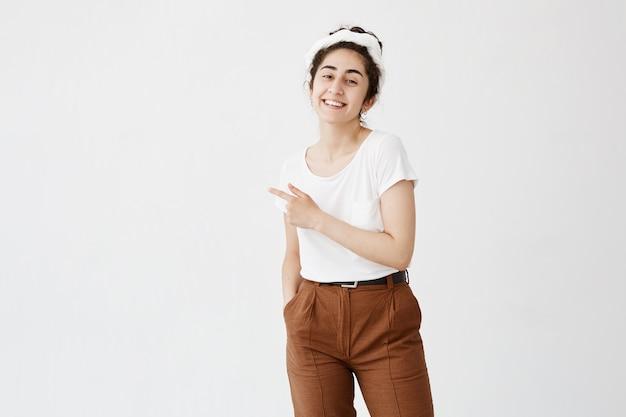 広告の概念。白い空白の壁のコピースペースでお団子ポインティング人差し指で巻き毛を持つ陽気な笑顔の若い女性の屋内ショット