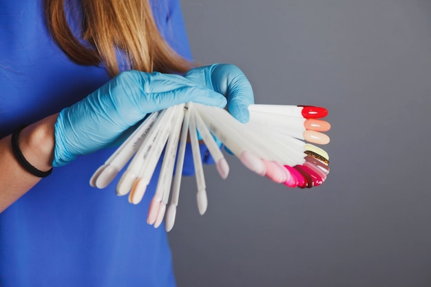Рекламная концепция маникюра и ухода за ногтями. женщина-мастер в салоне красоты проводит цветовую проверку лаков для ногтей разных цветов и выбирает их для покраски. образцы педикюра. копировать пространство