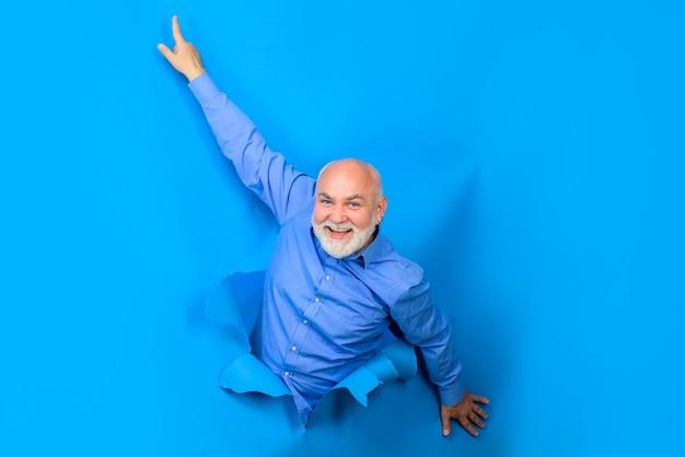 Реклама возбужденного бородатого мужчины проделывает дырку в бумажной вставке или слогане через бумажную копию