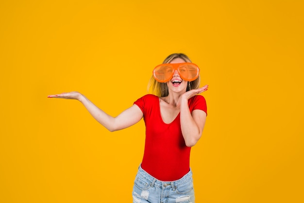 Advertising excited woman holds something look over here add sales and discount season sale funny