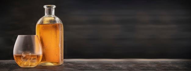 バーのウェブサイトの広告-スコッチ、バーボン、またはウイスキーをテーブルに置いたボトルとグラス。空のコピースペース、パノラマ