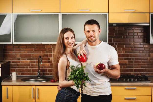 健康食品の広告、キッチンスタジオでポーズをとるかわいい若者。野菜と果物を手に持って、笑顔でカメラ目線の男女