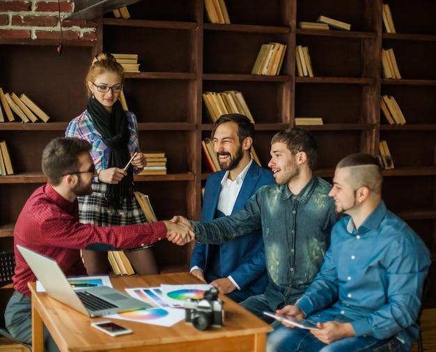 Менеджер по рекламе рукопожатием здоровается с заказчиком