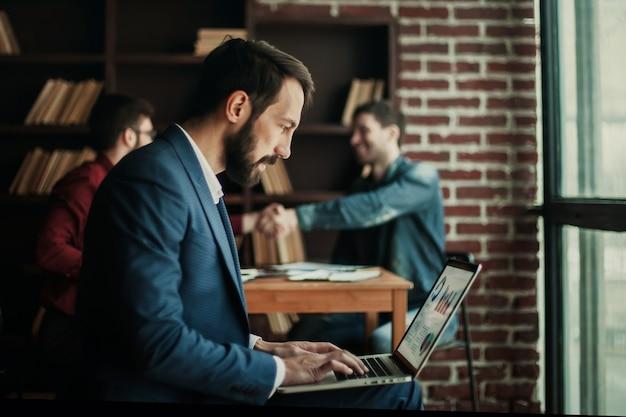Менеджер по рекламе работает с маркетинговой графикой на ноутбуке