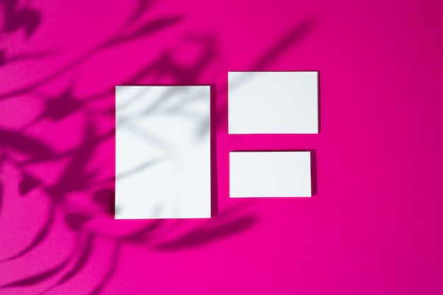 Advertising mock-up. white blank businesscards on bright pink background