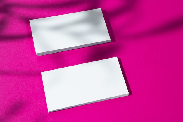 Рекламный макет. белые пустые визитки на ярко-розовом фоне