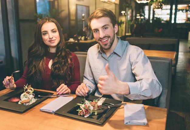 테이블에 앉아 있는 남녀의 광고 사진에 음식이 올려져 있습니다. 그들은 카메라를 찾고 웃고 있습니다. 남자는 그의 큰 엄지손가락을 보이고 있다