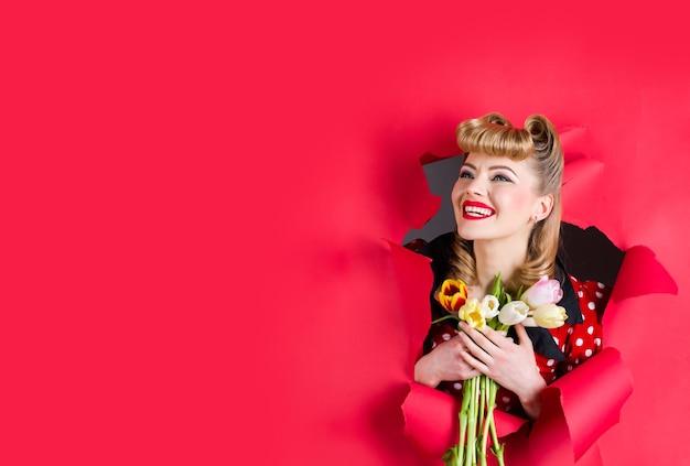 Реклама. подкалывать девушку с цветами. улыбаясь ретро женщина держит цветы через отверстие в бумаге. женщина через отверстие. приколите девушку. скопируйте пространство. место для текста.