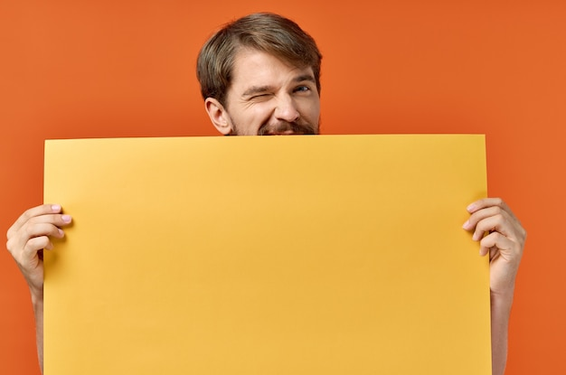 Advertising sign poster mockup man in the background orange background copy space. high quality photo