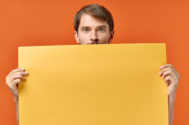 Advertising sign poster mockup man in the background orange background copy space.