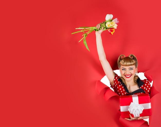 Реклама улыбающаяся девушка с цветами через отверстие в бумаге копирование места для текста подарки и подарок
