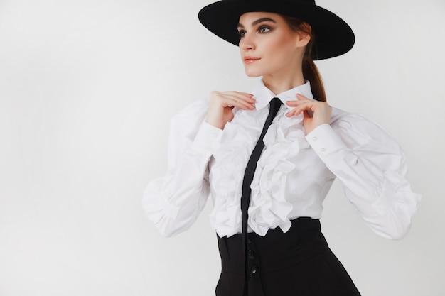 Реклама стильной милой молодой предприниматель в черной элегантной блузке и шляпе на белом светлом фоне. женщина в модной одежде позирует. понятие стиля, моды, красоты и достижения целей