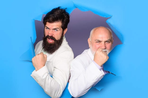 Успешные в рекламе мужчины смотрят сквозь дырку в бумаге бородатые мужчины выглядывают из разорванной бумаги