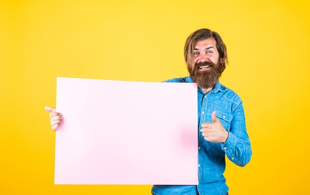 Advertising your product. human emotions. unshaven guy with groomed long hair. barbershop and hairdresser. male beauty and fashion. happy bearded man. brutal caucasian hipster hold paper, copy space.