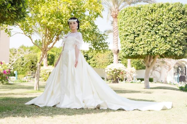 海外の結婚式の専門家からのアドバイスとヒント。おとぎ話のドレス。海外での結婚式を考えています。花嫁の愛らしい白いウェディングドレス晴れた日のヤシの木の背景。結婚式の熱帯の島。
