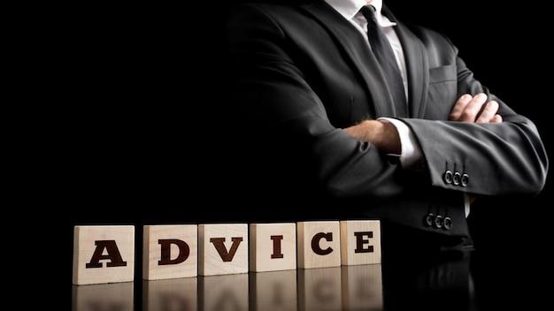 Письма с советами об организации небольших деревянных элементов с уверенным бизнесменом, скрещивающим руки перед телом, запечатленным на черном фоне