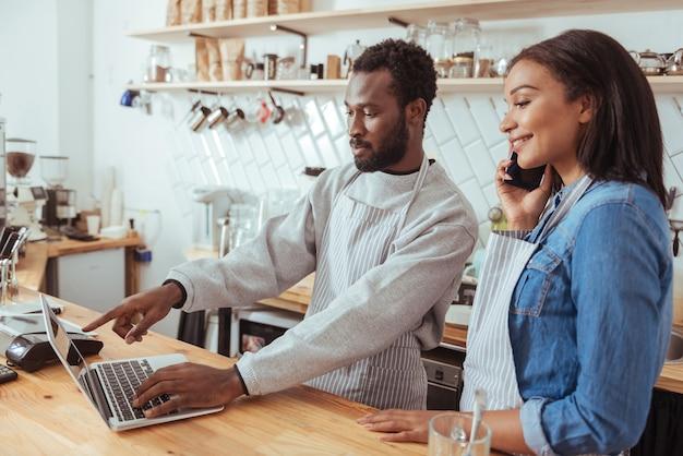 조언이 필요합니다. 카운터 뒤의 여성 동료 옆에 서서 여성이 누군가에게 전화하는 동안 웹 사이트의 메뉴 업데이트에 대해 조언을 구하는 매력적인 남성 바리 스타