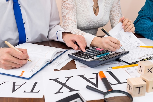 Advisor calculating and helping woman to fill 1040
