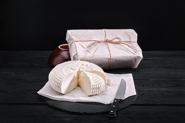 アディゲチーズは三角形の部分を切り落としました。近くには紙に詰められた3つのチーズヘッドがあります。木の板の上。背景の黒いコンクリート。上からの眺め。
