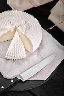 Adyghe 치즈는 삼각형 조각을 잘라