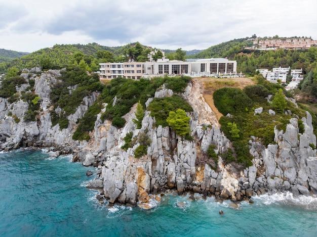 Costa del mar egeo della grecia, edifici di loutra situati vicino a scogliere rocciose, vegetazione e acqua blu. vista dal drone