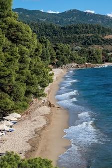 Costa del mar egeo della grecia, colline rocciose con alberi e cespugli in crescita, spiaggia con onde e ombrelloni con lettini