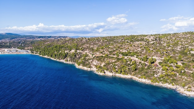 Aegean sea coast of greece, rocky hills with growing trees and bushes, few buildings near the shore