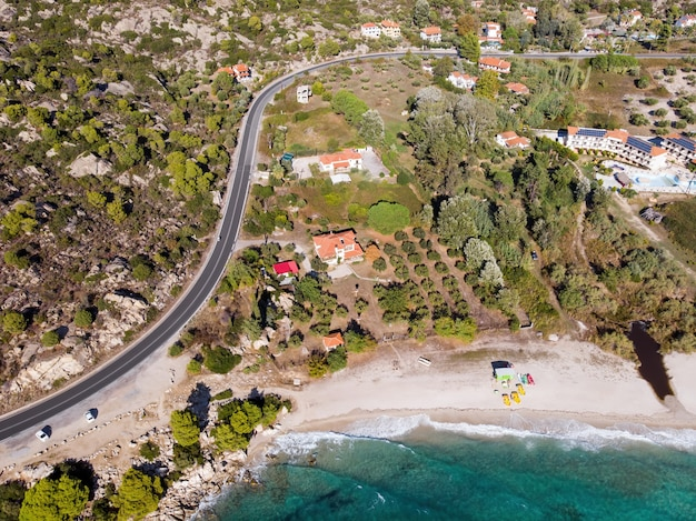 Aegean sea coast of greece, view of few buildings on the shore, greenery and resort