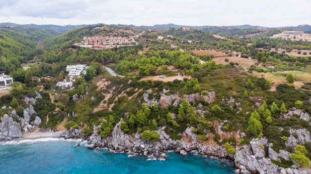 그리스의에게 해 연안, 바위 절벽, 녹지 및 푸른 물 근처에 위치한 loutra 건물. 드론에서보기