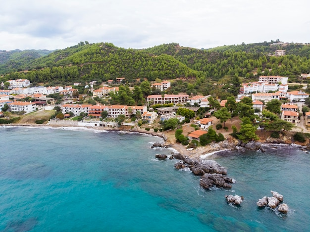 Эгейское море, побережье греции, постройки лутры, расположенные рядом со скалистыми утесами, зеленью и голубой водой. вид с дрона