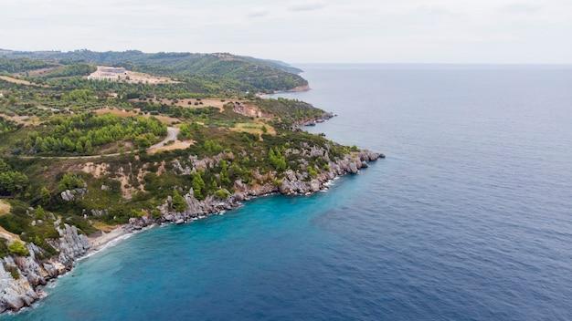 Эгейское море, побережье греции, скалистые утесы, зелень и голубая вода. вид с дрона