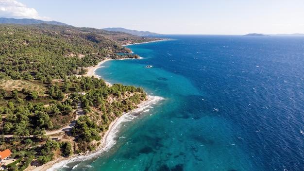 ギリシャのエーゲ海沿岸、木々や茂みが生い茂る岩だらけの丘、広大な水