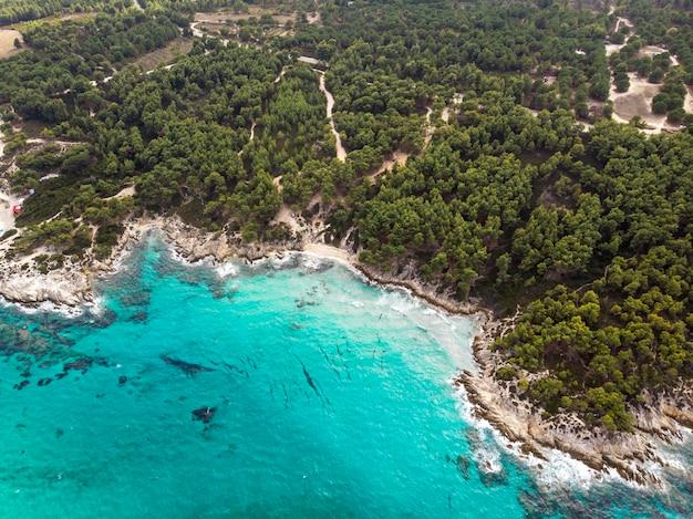 푸른 투명한 물, 주변의 녹지, 바위, 관목 및 나무가있는에게 해 해안, 무인 항공기, 그리스에서보기