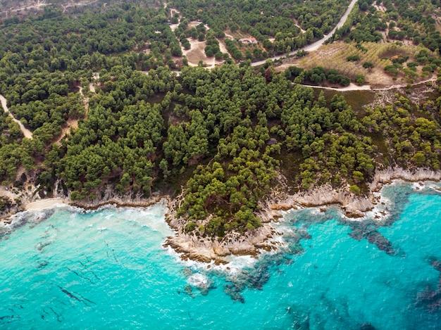 Побережье эгейского моря с голубой прозрачной водой, зеленью вокруг, скалами, кустами и деревьями, вид с дрона, греция