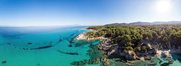 青い透明な水、周りの緑、岩、茂みや木々、ドローンからの眺め、ギリシャのエーゲ海の海岸