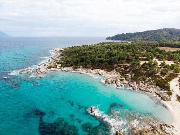Costa del mar egeo con acqua blu trasparente, vegetazione intorno, rocce, cespugli e alberi, vista dal fuco, grecia