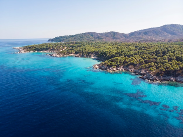 Aegean sea coast with blue transparent water, greenery around, rocks, bushes and trees, view from the drone, greece
