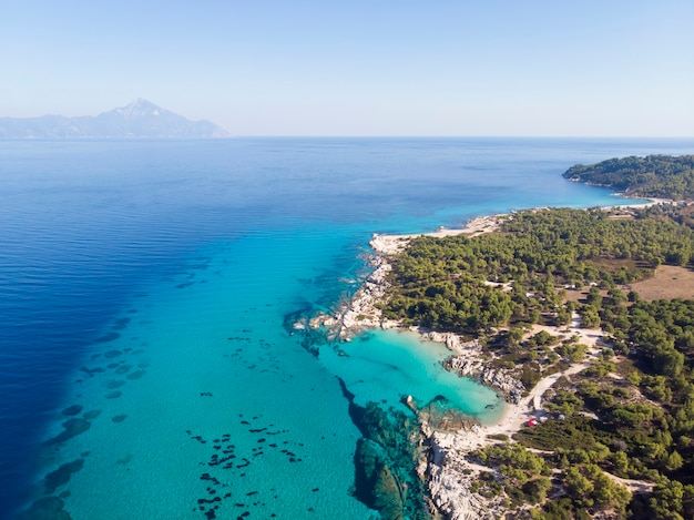 Aegean sea coast with blue transparent water, greenery around, rocks, bushes and trees, view from the drone, mountain  greece