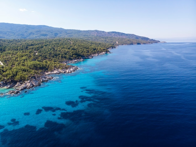 Aegean sea coast with blue transparent water, greenery around, view from the drone, greece