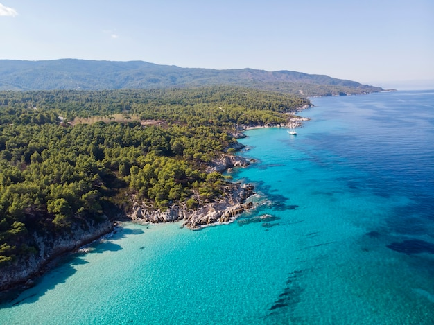 Aegean sea coast with blue transparent water and ship, greenery around, rocks, bushes and trees, view from the drone, greece