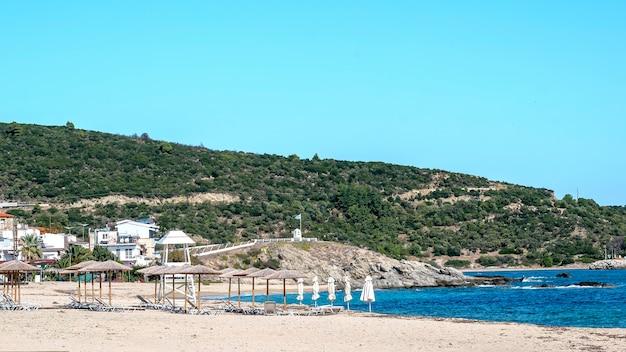 Побережье эгейского моря со зданиями слева, скалы, зонтики с шезлонгами, кусты и деревья, голубая вода с холмом в сарти, греция