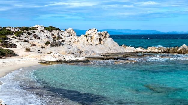 주변의 녹지, 바위와 덤불, 파도가있는 푸른 물, 그리스가있는에게 해 해안