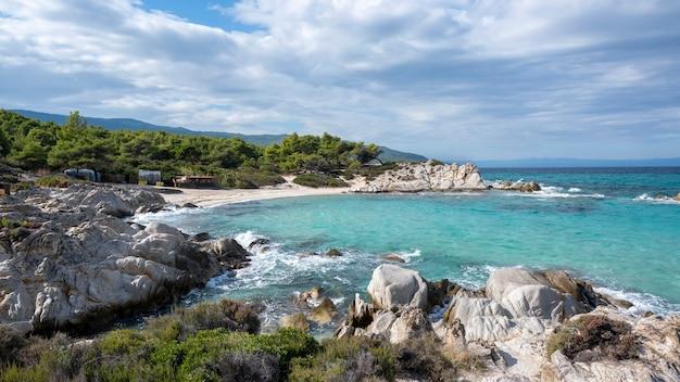 Побережье эгейского моря с зеленью вокруг, скалы, кусты и деревья, голубая вода с волнами, греция
