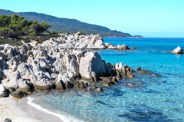 Aegean sea coast with greenery around, rocks and bushes, blue water and resting people, greece