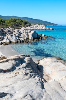 Aegean sea coast with greenery around, rocks, bushes and trees, blue water, greece