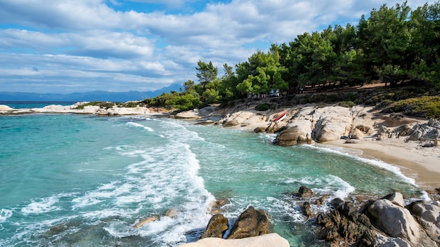 Aegean sea coast with greenery around, rocks, bushes and trees, blue water with waves, greece