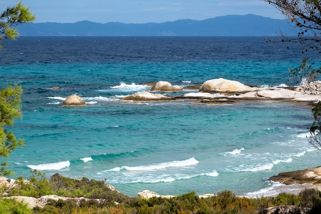 Aegean sea coast with greenery around, rocks and trees, blue water with waves, greece